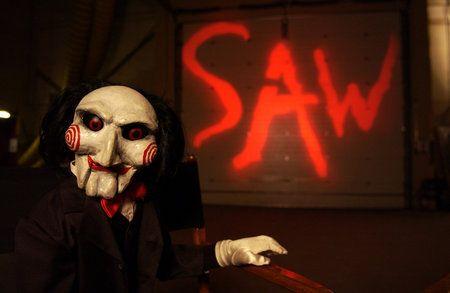"""Saw l'enigmista, 2004. Affidare tutta la malignità in un unico essere inanimato? Beh si può fare, questa volta la creatura è un bambolotto fatto a mano, terrore ne incute parecchio, soprattutto se sei legato su una sedia, incatenato e ti si accende una tv con impresso il simpatico pupazzo che t'intima un: """"Voglio fare un gioco con te, vivere o morire..."""". Gira su questo filone logico il film Saw l'enigmista che ha raggiunto quota 7 film nell'arco degli anni, intento nel punire la gente che non merita di vivere."""